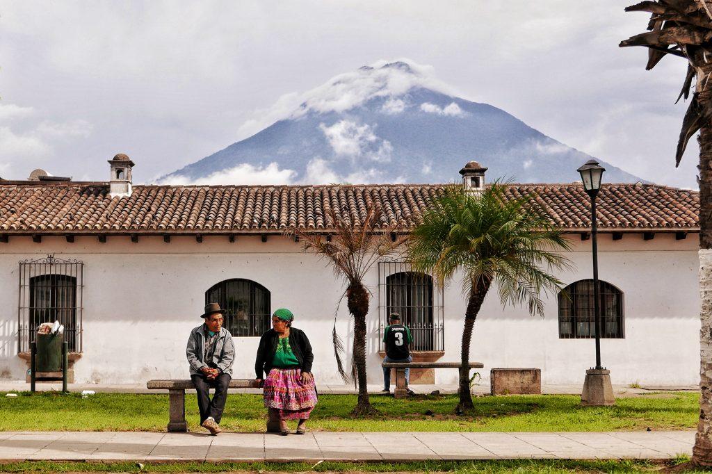 Una pareja de ancianos descansa con el volcán de agua de fondo.