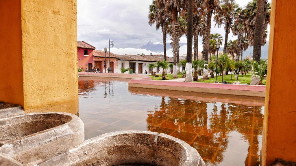 Por encima de las casas del Tanque de la Unión, plaza donde se lavaba la ropa popularmente, se eleva humeante el volcán de Fuego junto al altivo Acatenango.