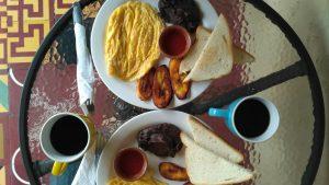 Huevo, pasta de frijoles, plátano frito, salsa de tomate y pan.